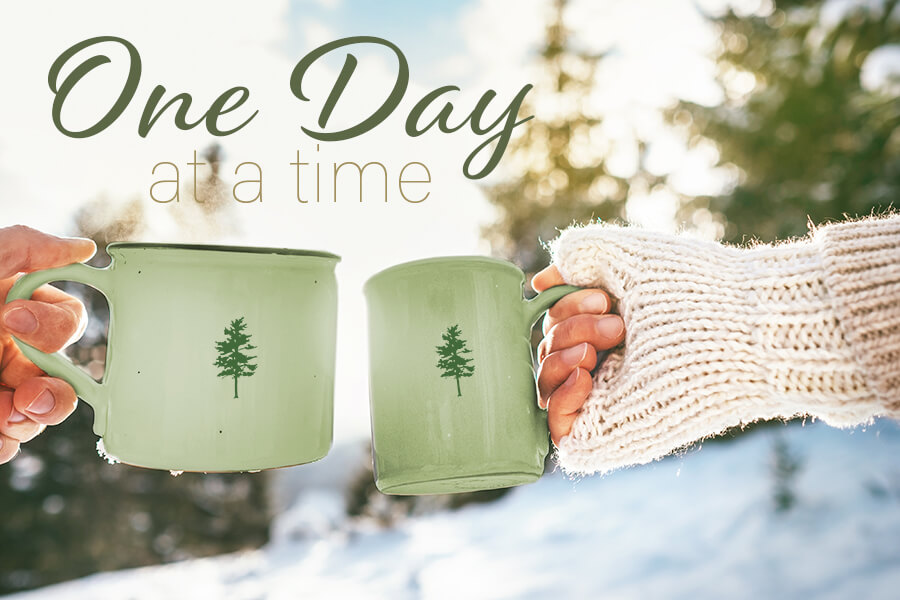 Man and woman hands in knitting mittens taking cups of hot drink. Sunny winter forest glade landscape on background