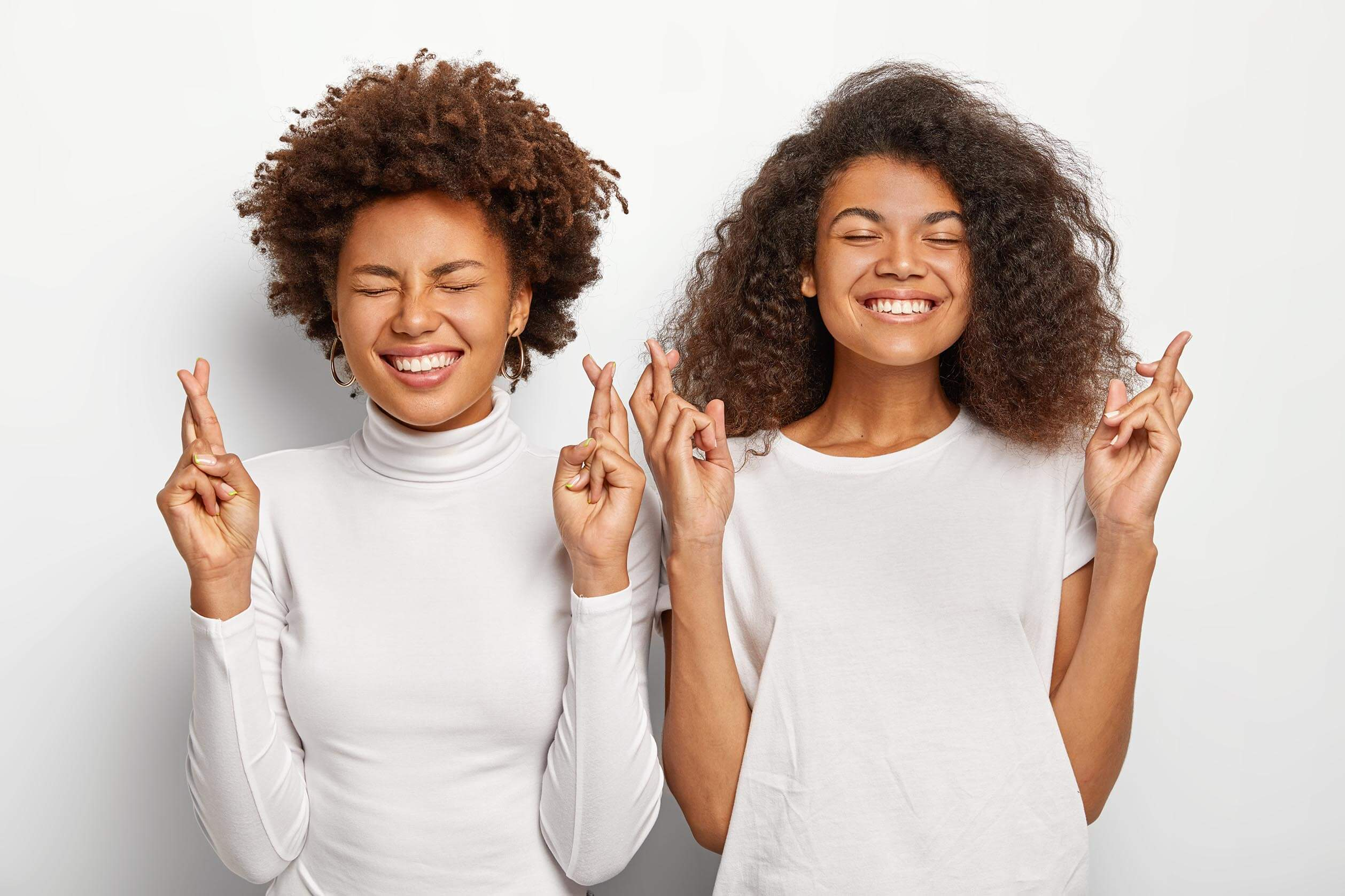 Two hopeful Afro American women pray wish come true, keep fingers crossed, smile broadly, dressed in white casual clothes, anticipate positive results, stand next to each other. Fullfill our dreams
